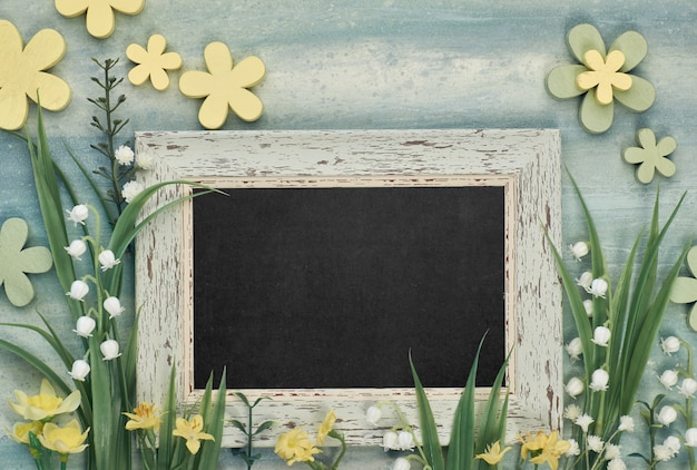 Blackboard framed with spring flowers on neutral background, space for your text