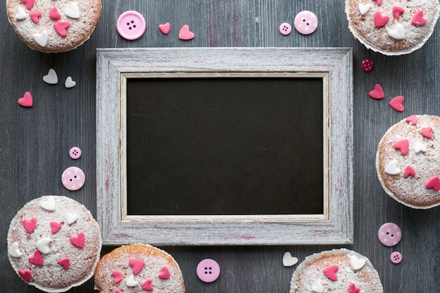 Blackboard framed with sugar-sprinkled muffins with pink and white fondant icing hearts