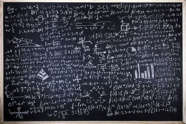 Blackboard inscribed with scientific formulas and calculations in physics and mathematics
