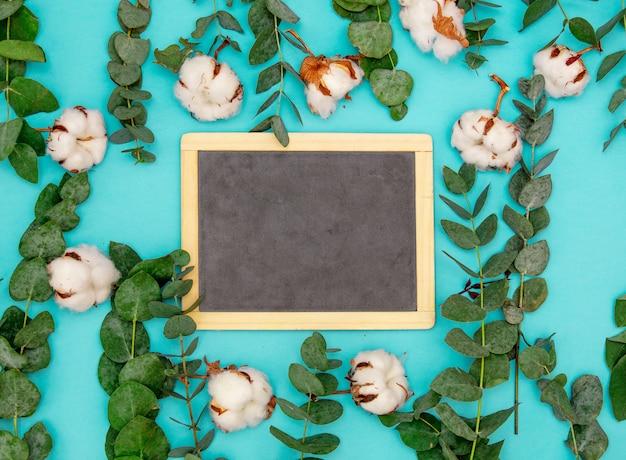 黒板は、ユーカリと綿の葉と枝の周りの青いテーブルの上にあります