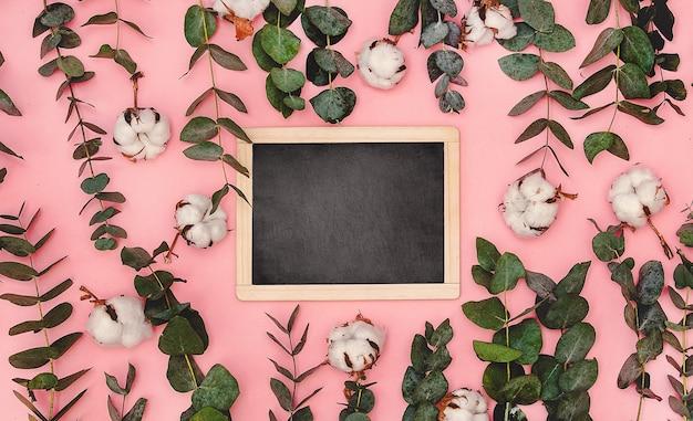 黒板は、ユーカリと綿の葉と枝の周りのピンクのテーブルの上にあります
