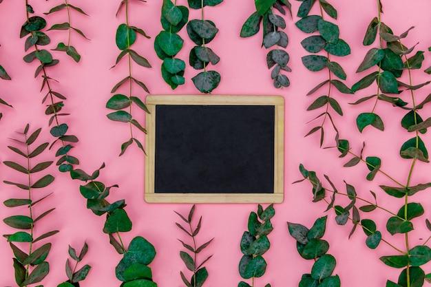 黒板はピンクのテーブルの上、ユーカリの葉と枝の周りにあります