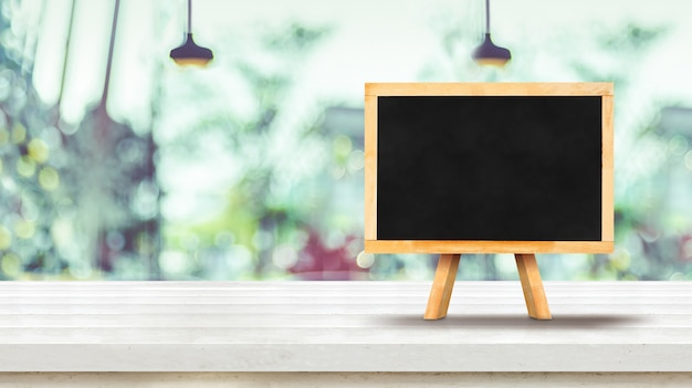 Blackboard menu on white plank wooden table top with blurred window of coffee shop
