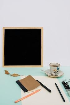 Blackboard near coffee and drawing supplies