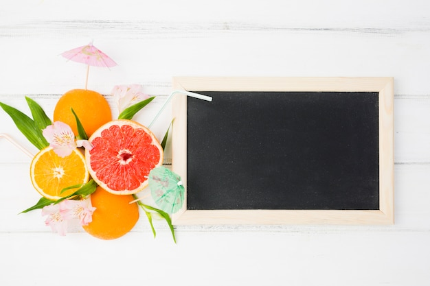 Blackboard near plant leaves and exotic fruits
