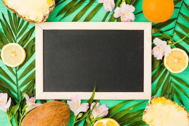 Blackboard near plant leaves with fresh fruits