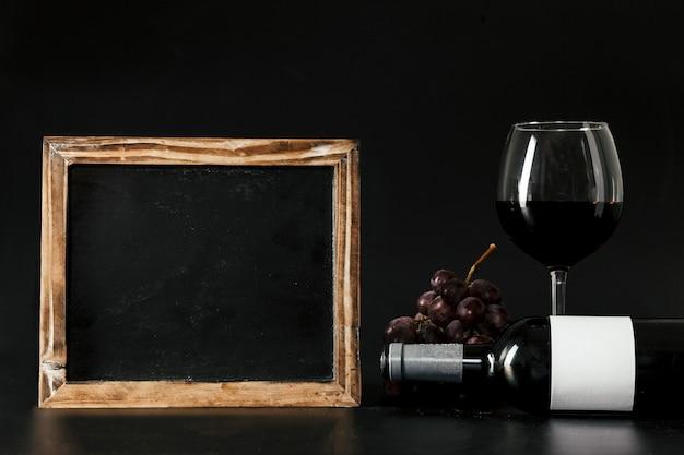 Blackboard near wine and grape