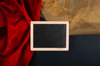 Blackboard on red and golden fabrics