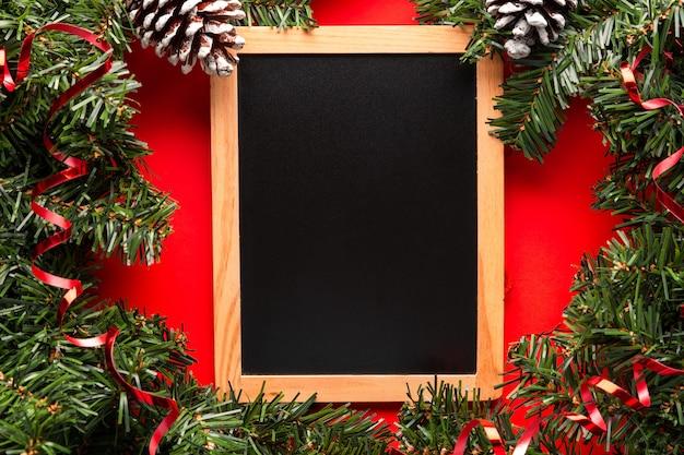 クリスマスの装飾が施された赤い背景の黒板は、ギフトリストや招待状のスペースをコピーします