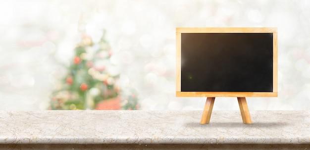 ぼかしボケクリスマスツリーの装飾で白い大理石のテーブルの上に黒板