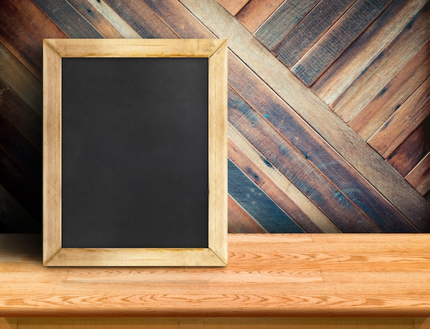 Blackboard on plank wooden table top at diagonal tropical wood wall
