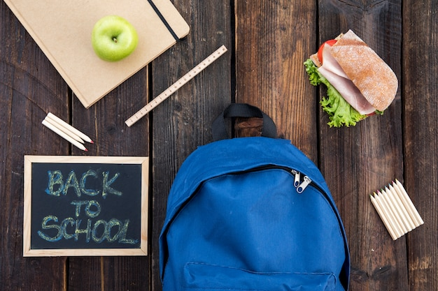 Blackboard, sandwich and school supplies