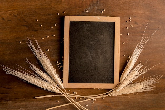 Blackboard and spike wheat on brown wooden table