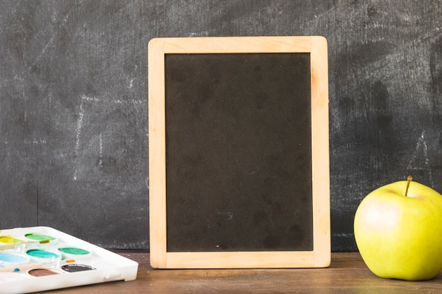 Blackboard on table with paints and apple