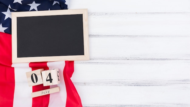 Blackboard usa flag and wooden cubes lying on table