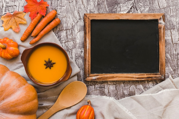 Blackboard and vegetables near soup