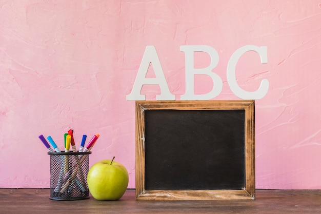 Blackboard with alphabet letters on table