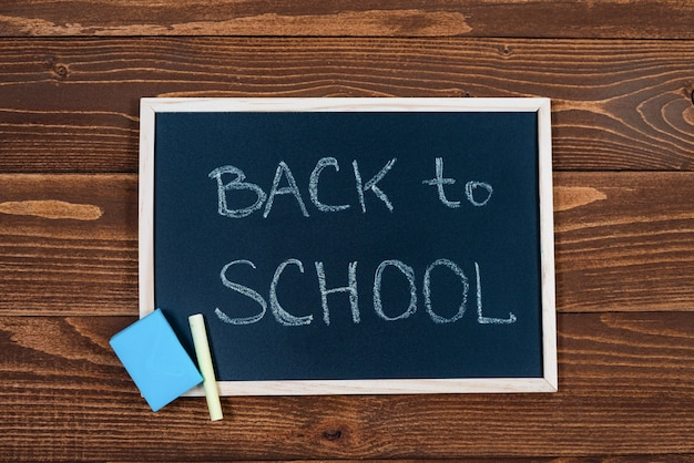 Blackboard with back to school text, chalk and sponge on a wooden.