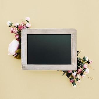 ゴールドウェディングの背景に美しい花と黒板