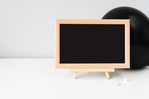 Blackboard with chalk in front of black balloon