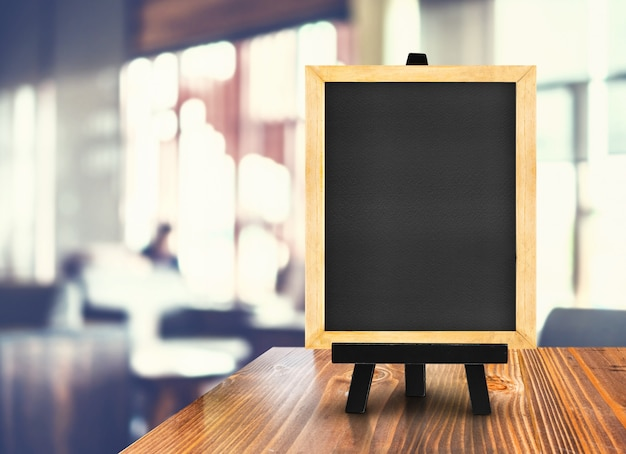 Blackboard with easel on wood table at blurred coffee shop background.