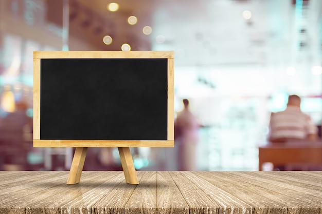 Blackboard with easel on wooden table with blur restaurant