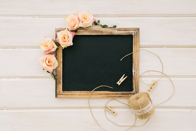 Blackboard with flowers and cord with clothespins
