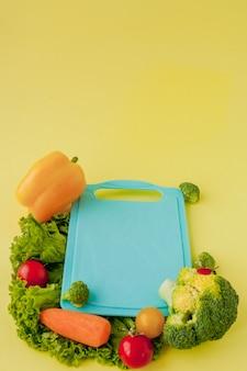 黄色の背景に新鮮な野菜と黒板。健康的な食事のコンセプト
