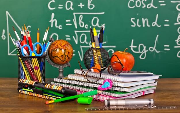Доска с пеналом и школьным оборудованием на столе
