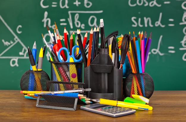 Blackboard with pencil-box and school equipment on table