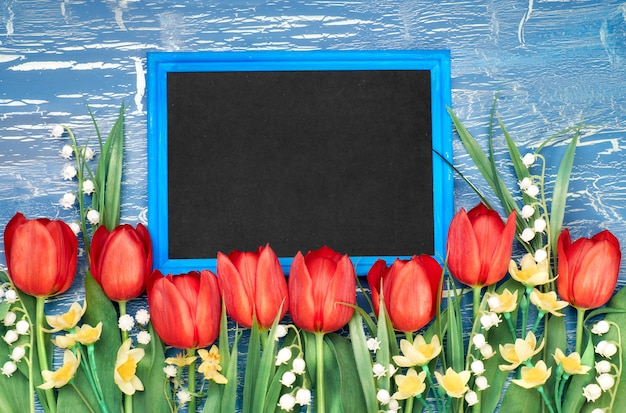 Blackboard with red tulips and lily of the valley flowers on blue rustic background, copy-space