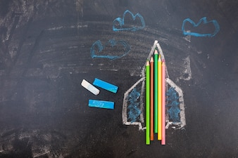 Blackboard with rocket and pens
