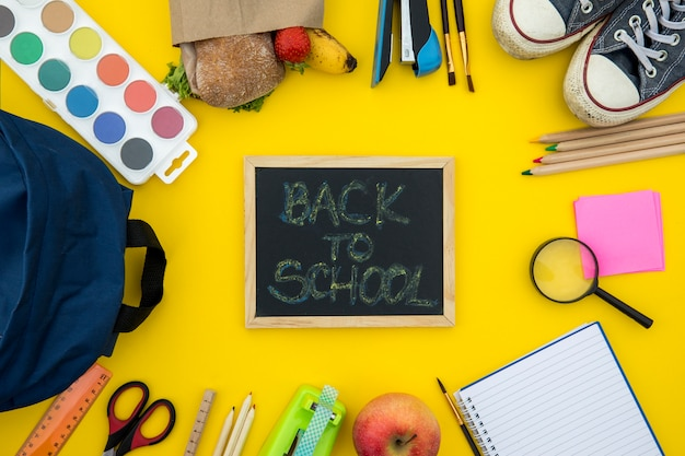 Blackboard with school accessories on yellow background