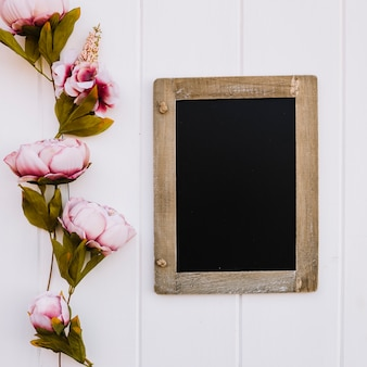 Blackboard with space for mock up with beautiful roses on the left