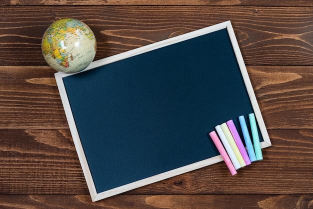テキスト用のスペース、地球儀、木製の背景に色付きのクレヨンのセットと黒板。