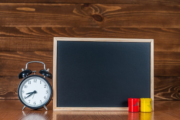 A blackboard with space for text, colored paint and an alarm clock on wooden.