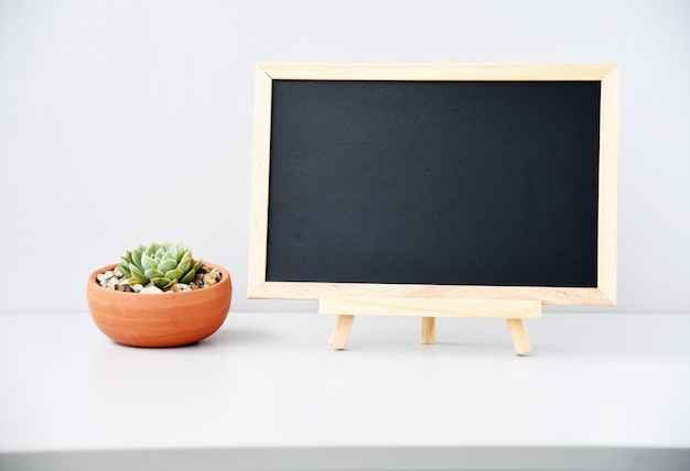 Blackboard with succulent plants and cactus on the table copy space