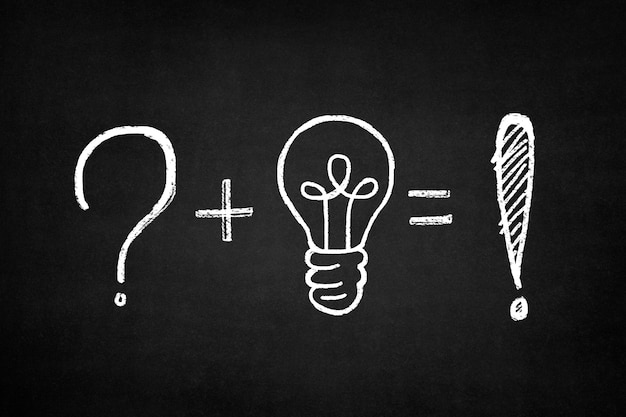 Blackboard with a sum of a question mark and a light bulb