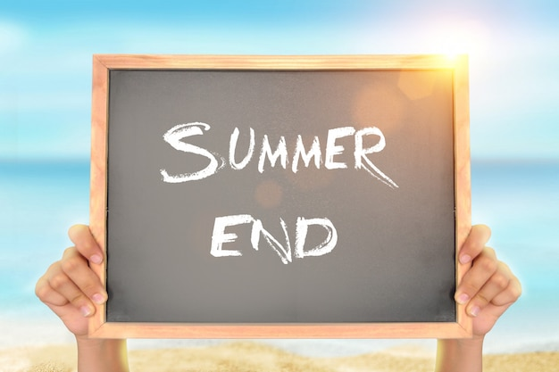 Blackboard with summer end text on the beach