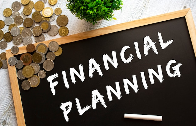 Blackboard with the text financial planning and metal coins on a gray wooden table. financial concept.