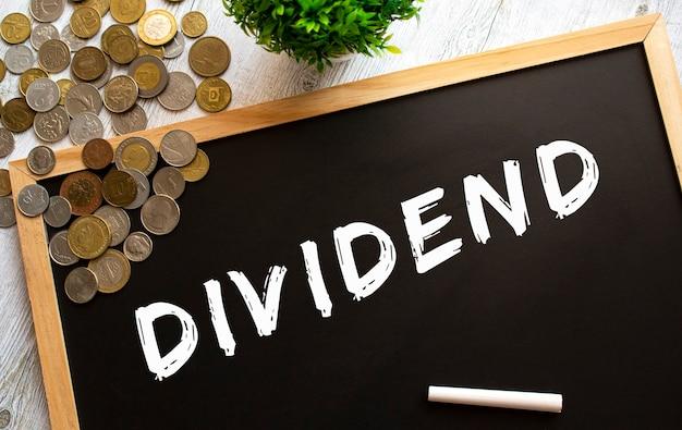 灰色の木製のテーブルに「dividend」というテキストと金属製のコインが書かれた黒板。