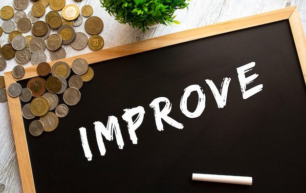 灰色の木製テーブルに「改善」というテキストと金属製のコインが書かれた黒板。財務コンセプト。