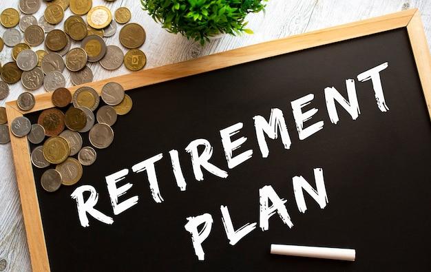 灰色の木製のテーブルにテキスト退職計画と金属コインと黒板