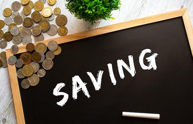 灰色の木製のテーブルに「節約」というテキストと金属製のコインが書かれた黒板。