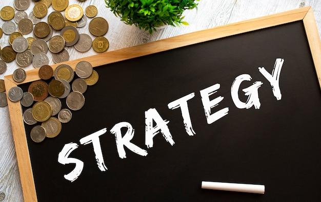灰色の木製のテーブルにstrategyと金属のコインというテキストが書かれた黒板