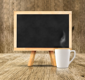 Blackboard with white hot coffee cup at wooden room