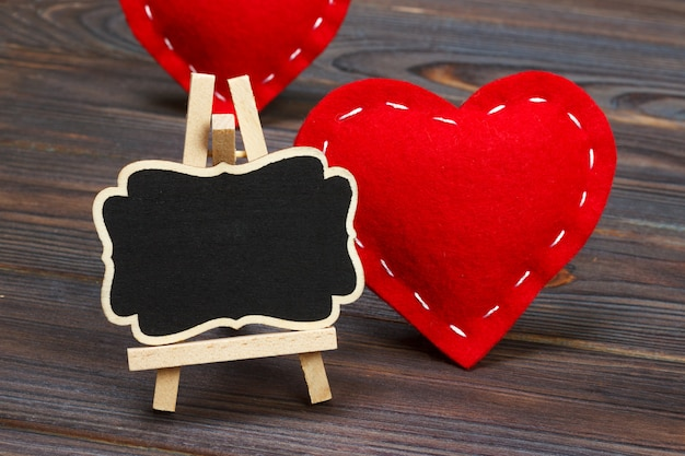 Blackboard on wooden background with red heart.