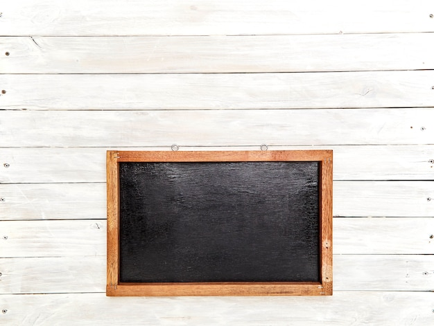 Blackboard in wooden frame on wooden wall