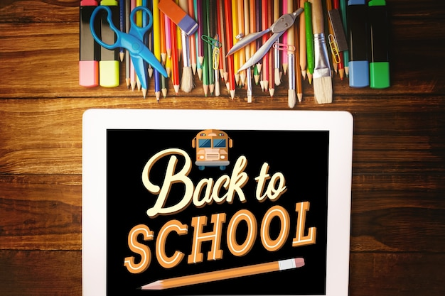 Blackboard over wooden table with school supplies