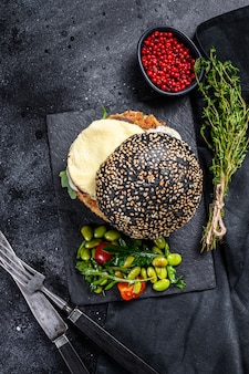 Домашнее ремесло бургер с черной булочкой, яичницей и рукколой. blackburger. черный фон. вид сверху